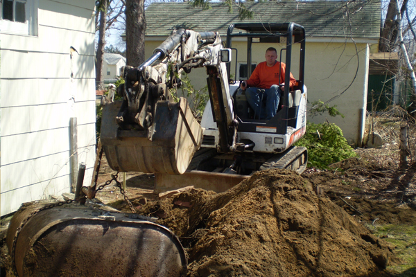 backhoe removing oiltank